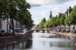 De Rapenburg gracht in Leiden. Met het torentje van de Universiteit op de achtergrond.